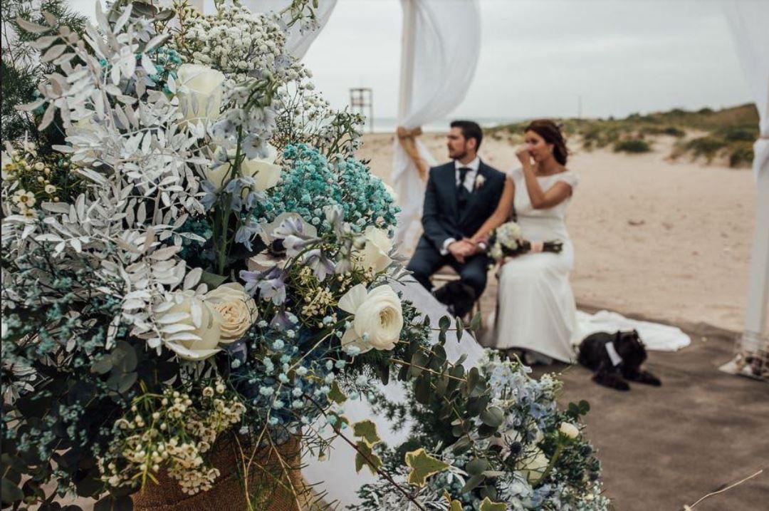 Boda en la playa con flores en azul y blanco